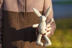 Conejo suave del juguete en las manos del walkink de la muchacha en parque de la caída Imágenes de archivo libres de regalías