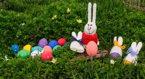 Conejo y huevos de Pascua divertidos con los sombreros hechos punto del conejito en hierba verde Pascua feliz Imágenes de archivo libres de regalías