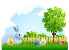 Conejo y huevos de Pascua en la hierba verde del jardín