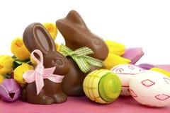 Conejos de conejito del chocolate de Pascua con los huevos rosados, blancos y verdes Fotos de archivo libres de regalías