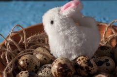 Conejos de Pascua y huevos de codornices en cuenco de madera en cierre del fondo para arriba Foto de archivo