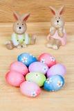 Conejos divertidos de cerámica con los huevos de Pascua adornados con las margaritas Foto de archivo