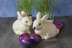 Conejos y huevos de la decoración de Pascua en un fondo de madera gris Imagen de archivo