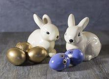 Conejos y huevos de la decoración de Pascua en un fondo gris Foto de archivo libre de regalías