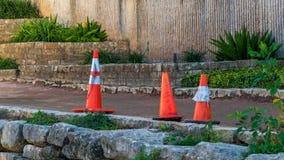 Cones alaranjados do tráfego perto da borda de um segmento urbano de um rio imagens de stock