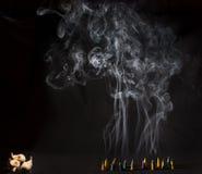Cones ardentes do incenso com fumo intenso no fundo preto Foto de Stock