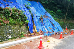 Cones barricade dangerous collapsed eroded hill slope area. Erosion because of tropical rain and thunderstorm royalty free stock photography
