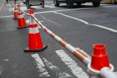 Cones da rua com bloco de conexão fora das barras imagens de stock royalty free
