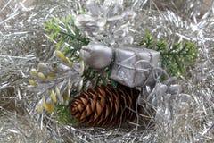 Cones do presente e do pinho em um ouropel prateado Imagem de Stock Royalty Free