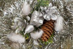 Cones do presente e do pinho em um ouropel prateado Fotografia de Stock