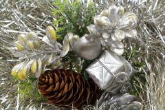 Cones do presente e do pinho em um ouropel prateado Imagem de Stock