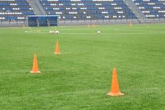 Cones e bolas para o treinamento do futebol no estádio Ostenta o fundo Imagens de Stock Royalty Free