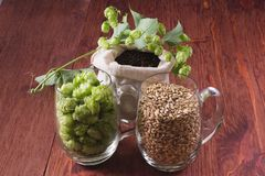 Cones of hops, pale caramel malt in glass mugs and chocolate malt in bag, closeup. Ingredient in craft beer brewing from grain ba stock photo