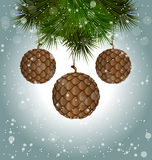 Cones like christmas balls hanging on pine branches in snowfall. Brown cones like christmas balls hanging on pine branches in snowfall isolated on white Royalty Free Stock Photos