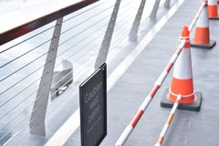 Cones in a line on a bridge. Caution sign on the Royalty Free Stock Photos
