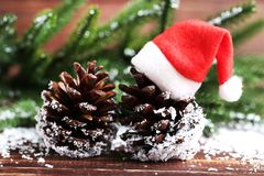Cones with santa claus hat and branches. Cones with santa claus hat and fir tree branches on wooden table stock images