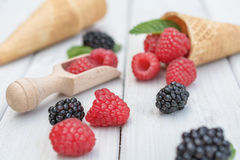 Cones and spoon with raspberries, blackberries and a twig mint s. Pread over a white table top Royalty Free Stock Photos