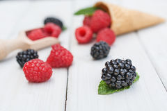 Cones and spoon with raspberries, blackberries and a twig mint s. Pread over a white table top Royalty Free Stock Photo