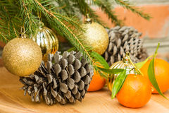 Cones, tangerines and Christmas balls on spruce branch Royalty Free Stock Image