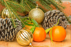 Cones, tangerines and Christmas balls and spruce branch Royalty Free Stock Image