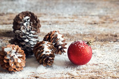 Cones vermelhos do pinho do ornamento do Natal em de madeira Fotografia de Stock