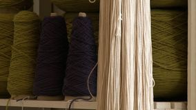 Cones of yarn on a shelf behind a skein. Different colored cones of yarn on a shelf behind a skein hanging on the edge of the shelf stock footage