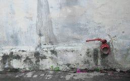 Conexión roja de la manguera en la pared vieja imágenes de archivo libres de regalías