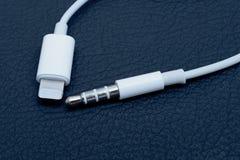 Conexión y 3 de la iluminación conector de audio de 5 milímetros en fondo azul Imágenes de archivo libres de regalías