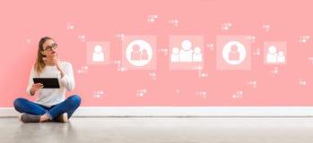 Conexiones sociales con la mujer que usa una tableta fotos de archivo