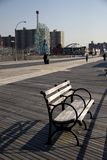Coney island. And a bench in the afternoon sun with The Wonder Wheel and Astroland Park in the background Royalty Free Stock Images