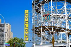 Coney Island, NY: Cyclone roller coaster curved tracks, with yellow sign royalty free stock images