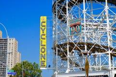 Coney Island, NY: Le montagne russe del ciclone hanno curvato le piste, con il segno giallo immagini stock libere da diritti