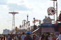 Coney Island, NY: Multidões que andam no passeio fotografia de stock