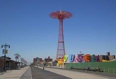 Coney Island-Promenade mit Fallschirmabsprung im Hintergrund Stockbilder
