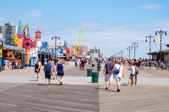 The Coney Island seaside boardwalk in New York on a beautiful su Stock Photos