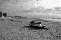 Coney island after storm. Jetski stands alone on the  ocean beach in the area of Coney Island  after storm ,without owner ,whose fate is unknown, debris around Royalty Free Stock Photo