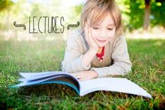 Conférences contre la lecture mignonne de petit garçon en parc images stock