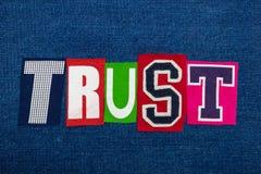 CONFÍE EN el collage de la palabra del texto en tela colorida en el dril de algodón azul, la confianza y la fidelidad fotos de archivo