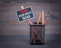Confíe en sus ideas locas Una pequeña tiza de pizarra y un lápiz coloreado en el fondo de madera fotografía de archivo libre de regalías