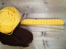 Confecção de malhas feito a mão de lãs amarelas e marrons Imagem de Stock