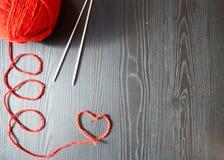 Confecção de malhas Linha vermelha no fundo de madeira Agulhas de confecção de malhas fotografia de stock
