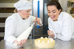 Confectioner apprentice nibbling whipped cream from cake Stock Images