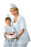 Confectioner with cake. Happy young confectioner in uniform with child assistant and decorative cake, white background Royalty Free Stock Image