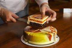 Confectioner cuts dacquoise cake in mirrored glaze. Modern cooking. Woman holds on knife piece of cake. Seen cakes and stuffing. Yummy royalty free stock photo