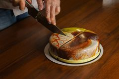 Confectioner cuts dacquoise cake in mirrored glaze. Home cooking. Modern cooking stock image