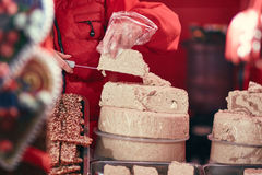 Confectioner cutting halva pieces. Confectioner in a Christmas market stand cutting pieces from halva wheel Stock Photo