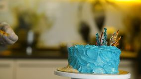 The confectioner decorates the blue cake in the nautical theme. stock video