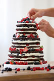 Confectioner decorates rustic naked wedding cake Stock Photos