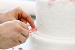 Confectioner decorates white wedding cake Royalty Free Stock Images
