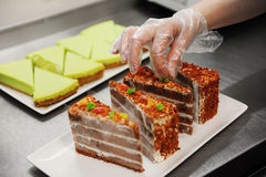 Confectioner is decorating chocolate cake Royalty Free Stock Photo